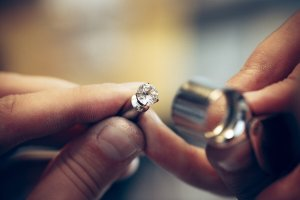 two hands repairing diamond ring