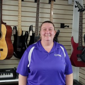 woman wearing purple with guitars in background