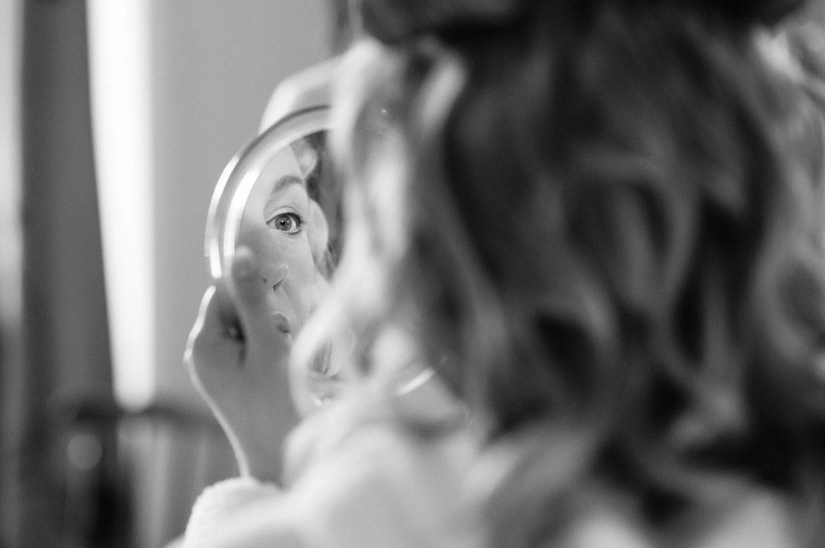 Bride checks her makeup in the mirror at the King John Inn