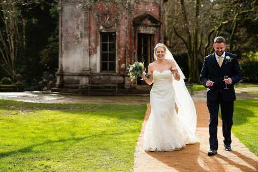 Happy bride walks with husband at Larmer Tree Gardens