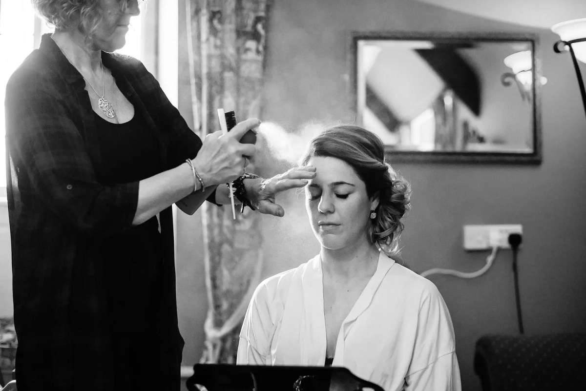Bride having her hair sprayed