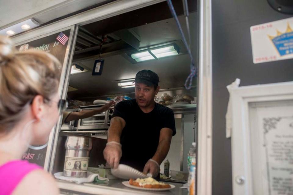 New York, 2015. július 31.  A magyar Prepuk Zsolt Lángos Truckjából kiszolgál egy vevõt a New York-i Wall Streeten 2015. július 27-én. Prepuk Zsolt Magyarországon autószerelõnek tanult, majd ingatlanosként dolgozott. 1999-ben, 24 éves korában érkezett New Yorkba, ahol 14 évig éttermekben dolgozott. A nemrégiben a The New York Times címû napilap gasztronómia rovata által dicsért, lángost árusító food truckot egy éve kezdte el építeni. Jelenleg a Lángos Truck a munkahelye, és két embernek ad munkát. Szintén magyar származású feleségével a napokban várják elsõ gyermeküket. MTI Fotó: Kallos Bea