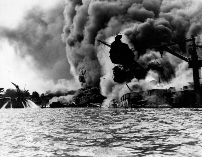 USS Arizona (BB-39) sunk and burning furiously, 7 December 1941. Her forward magazines had exploded when she was hit by a Japanese bomb. At left, men on the stern of USS Tennessee (BB-43) are playing fire hoses on the water to force burning oil away from their ship Official U.S. Navy Photograph, now in the collections of the National Archives.