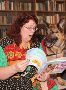 Woman reading book to German Shepherd dog.
