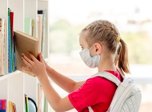 School girl in protective mask in library