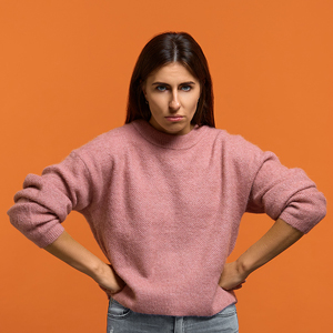 Young woman with long dark hair and angry expression in pink sweater against an orange wall.