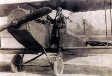 Bessie Coleman standing on the wheel and lower wing of a biplane, black and white image.