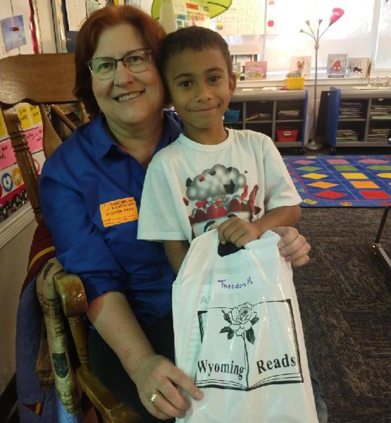 Brown-haired woman with eyeglasses and blue shirt in wooden chair holding young boy who is standing in front of her and holding a Wyoming Reads bag.