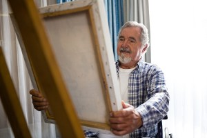 Senior man looking at painting while sitting on wheelchair