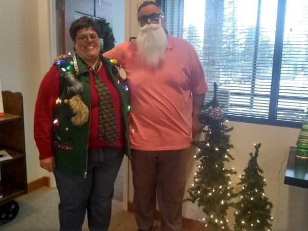 Rachael with decorated Christmas vest and Thomas in Santa beard in front of Christmas trees.
