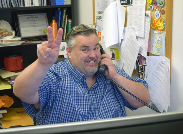 Thomas at his desk smiling, phone to his ear, holding up a peace sign.