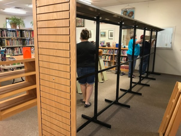 Partially assembled library shelves with three staff members behind them
