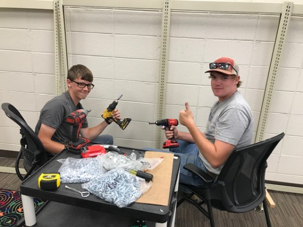 Two young men holding electric drills sitting at table with bags of hardware
