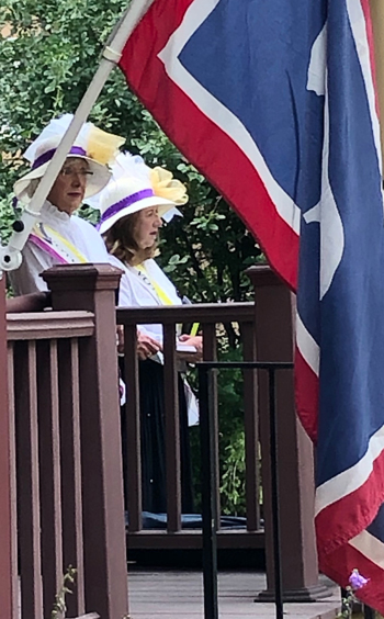 Two women in suffragist costume standing on dais with Wyoming flag in foreground.