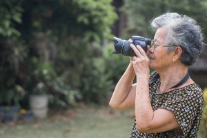 Senior woman with short gray hair wearing glasses and shooting photography by a digital camera at the park.