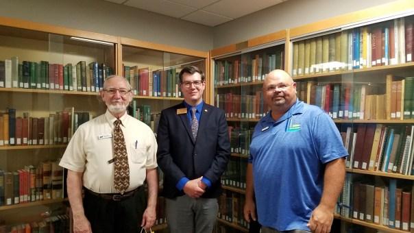 Three men standing in front of bookshelves.