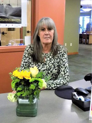 Eileen sitting at desk with flowers