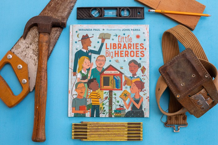 This is an image of the book, Little Libraries, Big Heroes, surrounded by building materials. The purpose of this image is to promote the book.