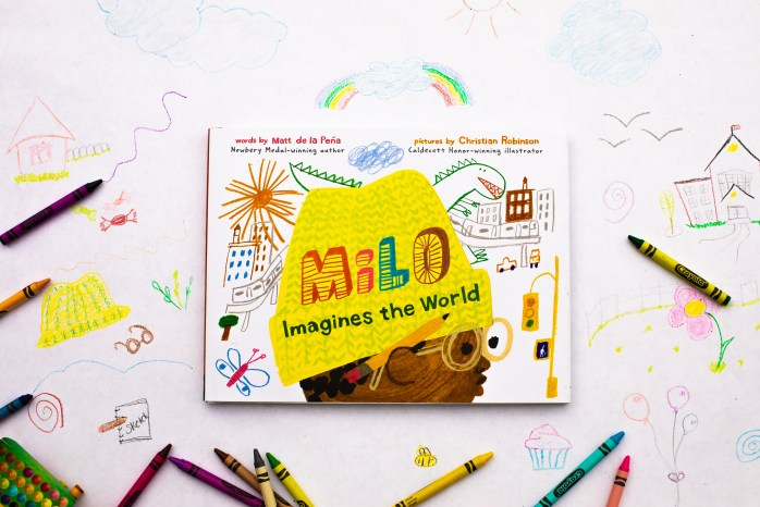 Promotional image for a lesson activity based on the book Milo Imagines the World. The cover of the book Milo Imagines the World by Matt de la Peña and Christian Robinson is featured in the center of the image. Crayons and crayon drawings surround the book.