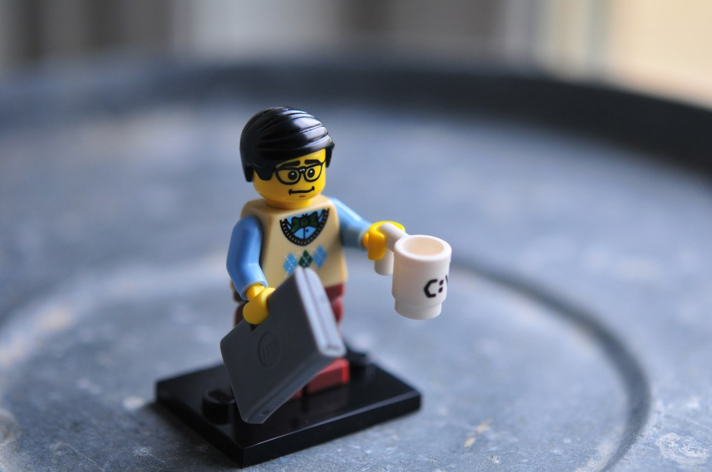 lego man holding laptop and coffee
