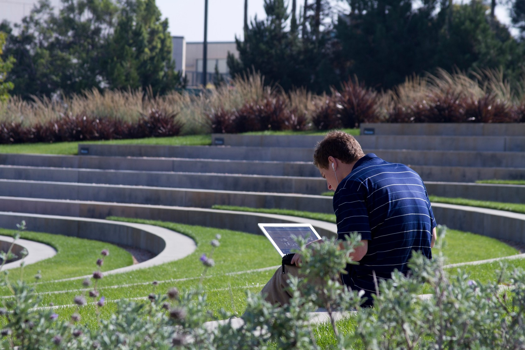 Student working on laptop outside the library