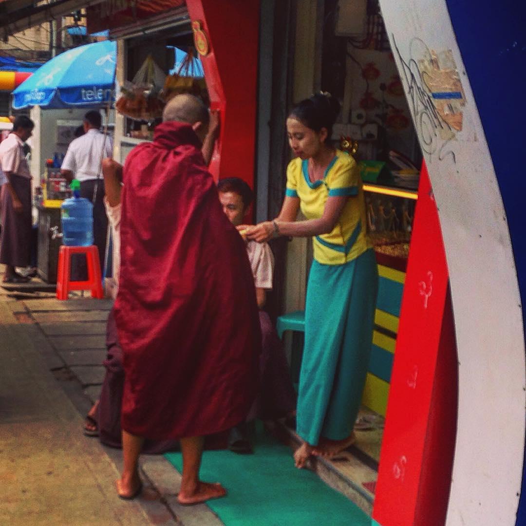 Rangoun, Birmanie. Cette femme fait don d'un peu de nourriture à un vieux bonze, puis joint les mains en un geste de respectueuse piété. Son visage est enduit de thanaka, une crème jaunâtre obtenue en râpant un morceau de bois sur une pierre avec un peu d'eau.