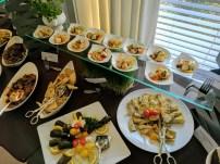 Scallops above, Mediterranean options like artichoke hearts, dolmades, pita bread, and caponata below