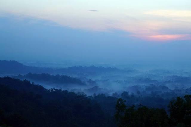 Candi Borobudur terlihat samar dikelilingi kabut tipis dari Punthuk Setumbu.
