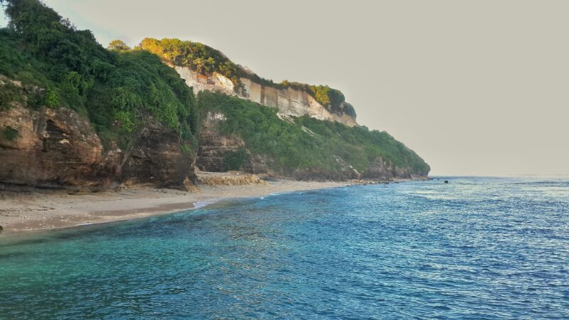 Tebing karang menjulang tinggi dan air laut yang tenang membuat pantai ini makin elok saja.