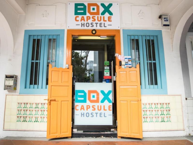 Bagian depan dari Box Capsule Hotel yang mencolok dengan warna orange dan biru muda