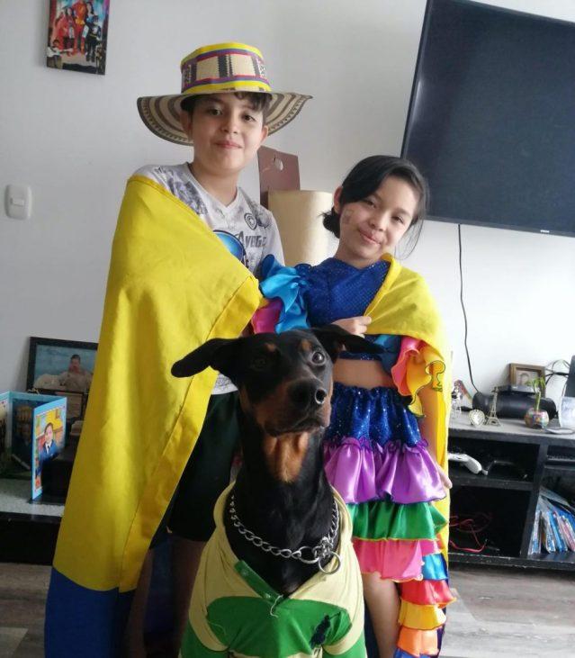 niño y niña estudiantes vistiendo bandera de colombia junto a su perro mascota