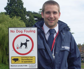 Steve Pearce holding one of the dog poop warning signs at Stowe Pool