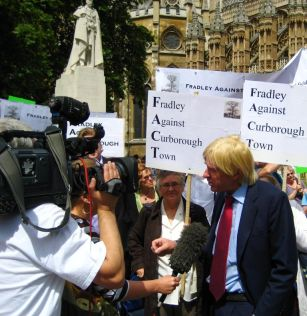 Michael Fabricant talking to the media with protestors