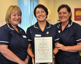 Julie Anne Hughes shows her award to colleagues