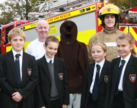 Maple Hayes students with firefighters and the mannequin used in the demonstration