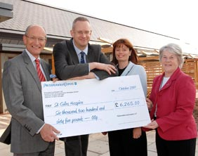Peter Holliday (left) and Laura Pennycuick (right) receive the donation from PricewaterhouseCoopers' Midlands Forensic Services Managers Andrew Meadows and Ansie Delport