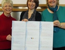 Governor Teresa Clarke (centre) receiving the panels from calligrapher Ursula McKay and Mysteries' Chair Ros Hallifax
