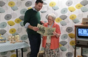 Richard Ernest, managing director of RemPods, looking at a 1950s magazine with hospital volunteer Brenda Bartram
