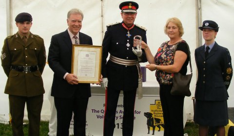 The Lord-Lieutenant Ian Dudson CBE,  Jane Dudson, James Whittaker and Christine Gilbert accepting the award and certificate on behalf of the museum volunteers, with two cadets from the Lieutenant's office