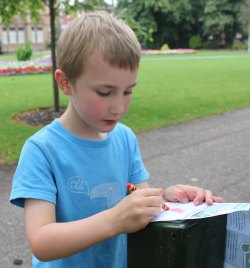 A youngster tries out the brass rubbing trail