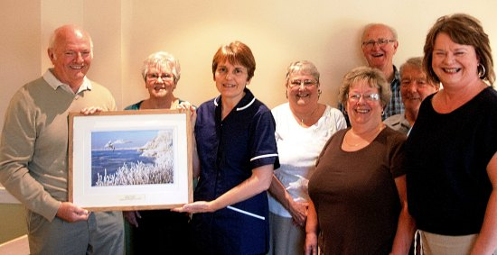 Members of Rugeley and Armitage Camera Club hand over one of the images to representatives from St Giles Hospice