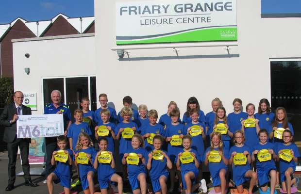 Members of Lichfield Swimming Club receive their new kit from Midland Expressway Ltd