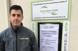 Jamie Richards from AEDdonate next to the damaged defibrillator cabinet