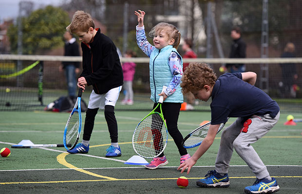 Young players try out a tennis coaching session