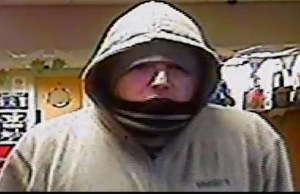 A CCTV image of the man with a Midlands accent who robbed a betting office in Newport