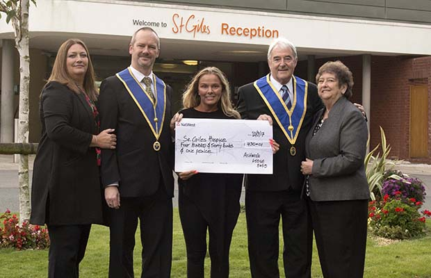 Clive and Pauline Andrews-Lewis, and Mike and Eunice Mason presenting the cheque to Carolyn Harris from St Giles Hospice