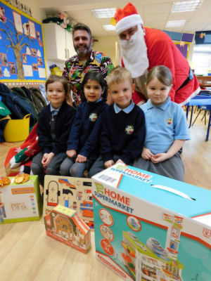 Teaching assistant Mr Heath with Father Christmas and children at St Stephen's Primary School in Fradley