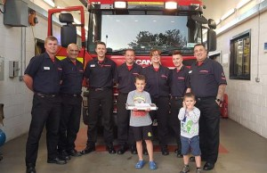 Firefighters receiving their doughnuts from a local Beaver Scout
