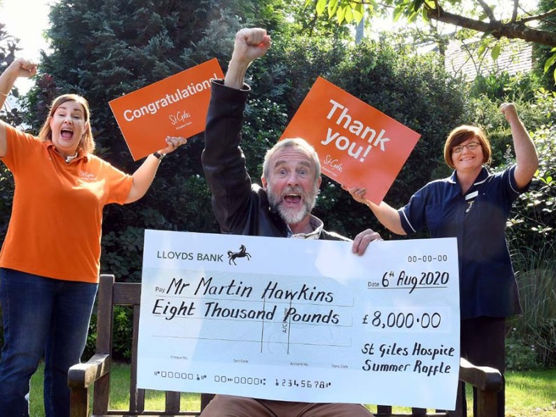 Martin Hawkins celebrates his lottery win with lottery manager Alison Jerram and ward manager Sharon Meehan