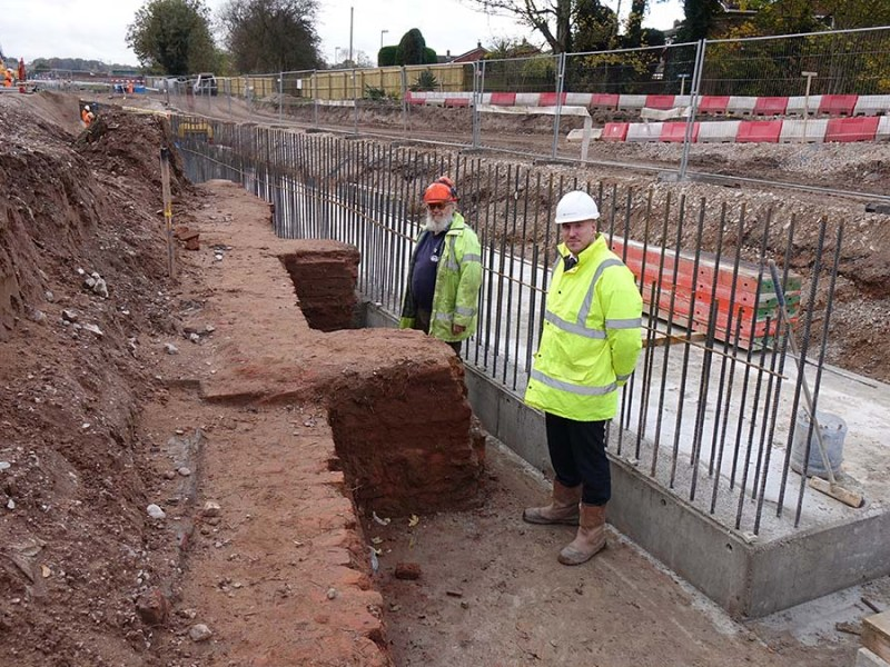 Peter Buck and Dan Hassall stand between the newly excavated Heritage Lock 23 and the concrete base for a retaining wall